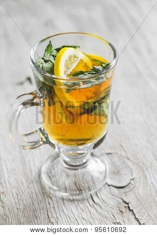 Green Tea With Lemon And A Rumpled In A Glass Mug On A Light Wooden Background