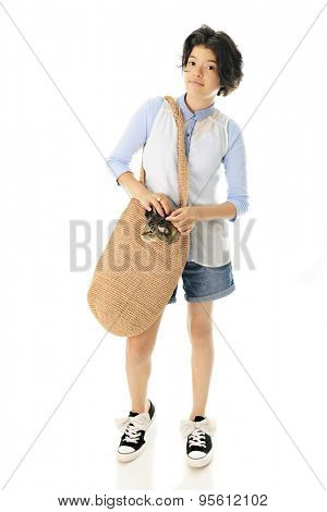 An attractive young teen taking a walk with her pet cat polking his head out of her tan shoulder bag.  Focus is on the girl.  On a white background.