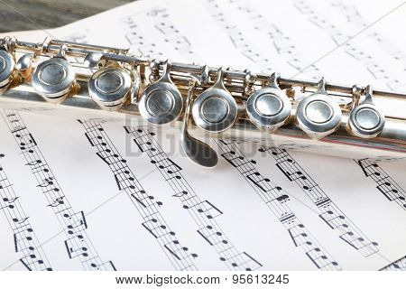 Silver flute on music notes background