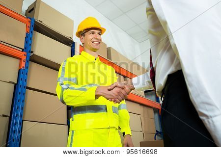 Happy Warehouse Worker Shaking Hands With Manager