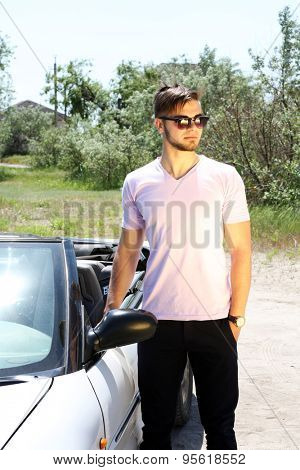 Young man standing near cabriolet, outdoors