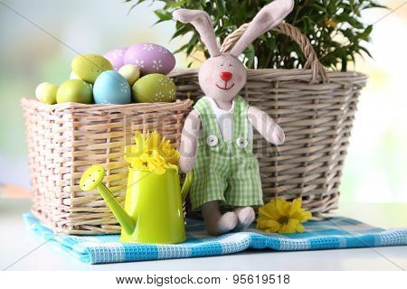 Easter bunny with painted Easter eggs with flowers on bright background