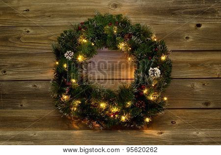 Christmas Wreath With White Lights On Rustic Wooden Boards