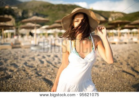 Young beautiful sexy tanned brunette woman wearing hat and elegant dress standing on beach