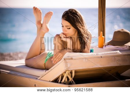 Smiling beautiful woman sunbathing in a bikini on a beach at tropical travel resort,SPF protection