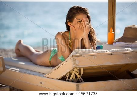 Shy woman peeking through covered face.Funny beautiful woman sunbathing in a bikini on a beach at tr