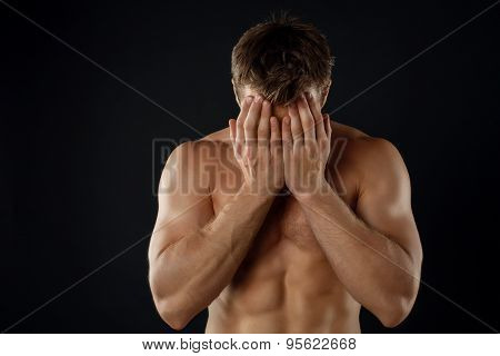 Attractive young male athlete is expressing shame