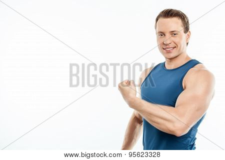 Attractive young sportsman is showing his strength