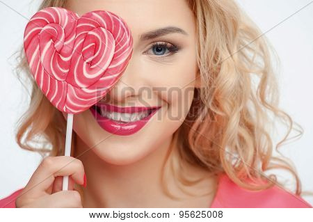 Attractive young woman is making fun with candy
