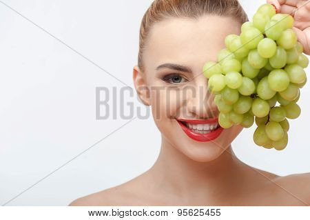 Beautiful young girl is making fun with fruit