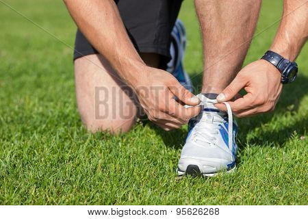 Fit young sportsman is tying his shoelaces