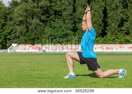Attractive young sportsman is doing warm-up on grass