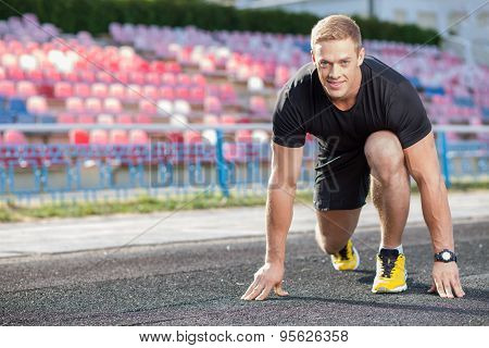 Attractive young sportsman is ready to run in stadium
