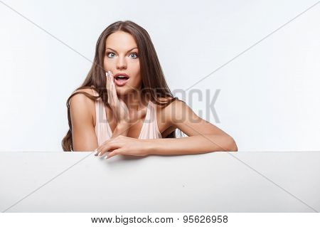 Pretty young girl is standing near horizontal surface