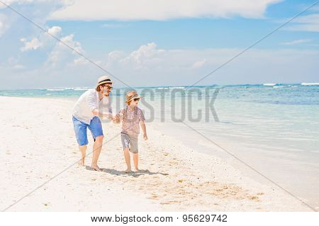 Young happy father and his little son enjoing summer time walking barefoot at the beach with ocean,