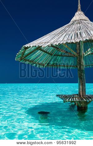 Bamboo beach umbrella with bar seats in the water of tropical island