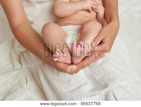 baby legs in mother hands on white background
