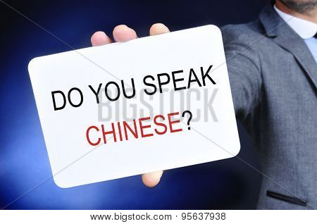 closeup of a man in a gray suit showing a signboard with the question do you speak chinese? written in it