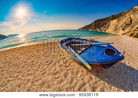Sunset with Old Blue Boat on Empty Myrtos Beach on Kefalonia Island of Greece