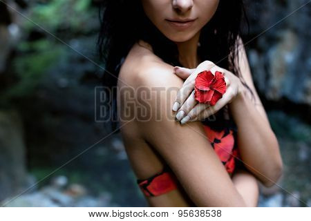 beautiful sexy cute girl with black hair in a wet bathing suit with a flower in her hair and a ring