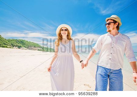 Happy young couple in hats and sunglasses walk at tropical beach with white sand against beautiful v