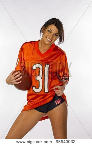 An attractive brunette model posing with a football in a studio environment