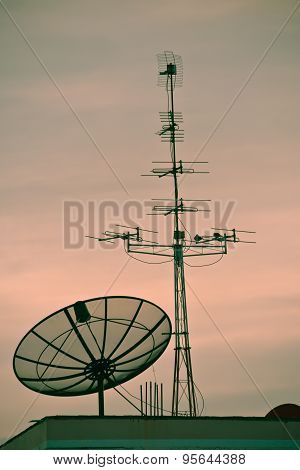 Tv Satellite Dishes And Antennas On Roof At Sunset.