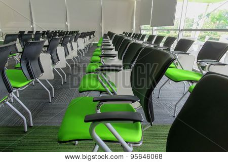 Many Green Chairs Arranged Neatly In A Training Room.