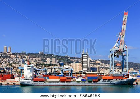 Various brands and colors of shipping containers stacked in a holding platform waiting for loading w
