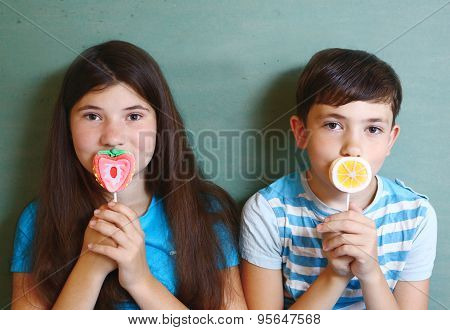 two marshmellow candy on stick designed as fruit orange and strawberry with smiling happy kids girl and boy on the background