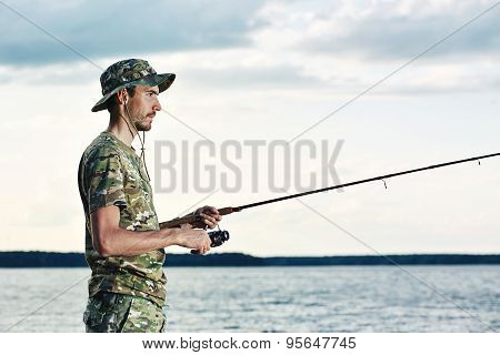 Young Man In A Camouflage Fishing On The Lake.