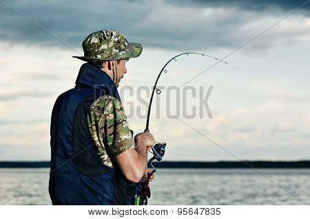 Close Up Back Portrait Of Man Fishing On The Lake During His Vacation