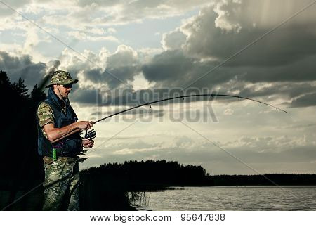 Surprised Man Fishing On The Lake During Sunset Outfit Of A Fisherman
