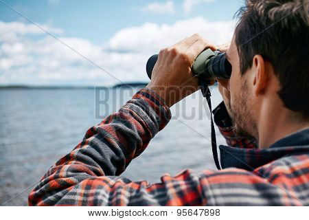 Close Up Back Portrait Man Looks Through Binoculars While Fishing At The Lake On Vacation