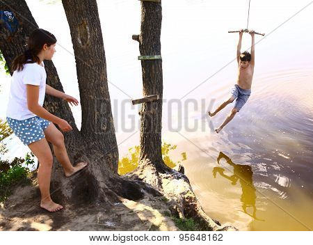 siblings brother and sister entertain themselfs with water swing on vacation