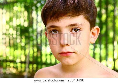 preteen boy close up portrait on summer green background