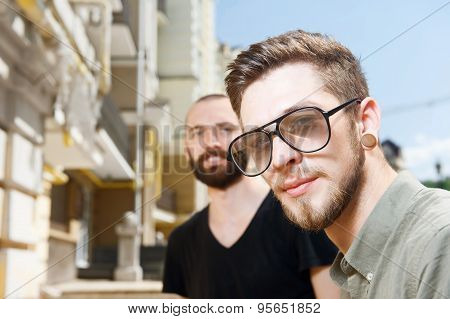 Attractive young men are walking across city