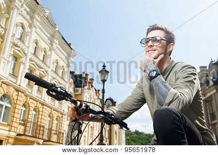 Handsome young hipster guy is cycling on street