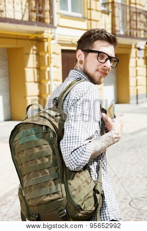 Attractive young hipster guy is walking across city