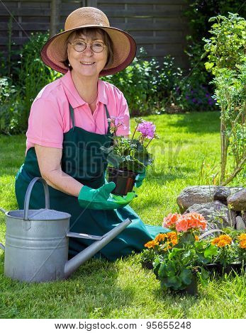 Active Senior Women Working In Her Garden