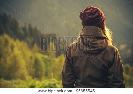 Young Woman standing alone outdoor with wild forest mountains on background