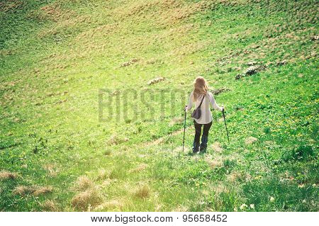 Young Woman with trekking poles hiking outdoor