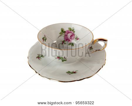 Porcelain teacup and saucer with floral rose ornament in classic isolated over white