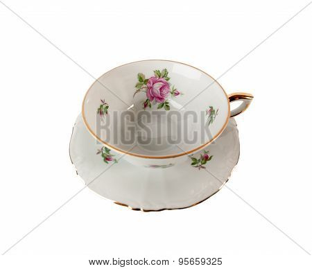 Porcelain teacup and saucer with floral rose ornament isolated over white
