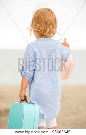 Cute little girl with her suitcase at the seaside standing on the beach looking out over the ocean with her back to the camera as she enjoys her summer vacation.
