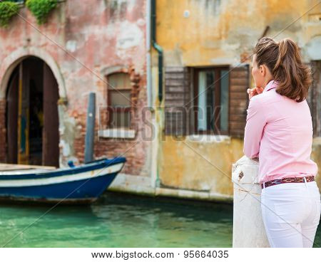 Woman Seen From Behind Looking Out Onto Canal In Venice
