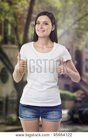 Brunette In Denim Shorts And White T-shirt, Thumbs Up. New York Neighbourhood In Blur On The Backgro