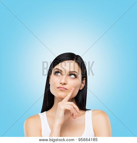 A Portrait Of A Pensive Brunette Lady In A White Tank Top. Blue Background.