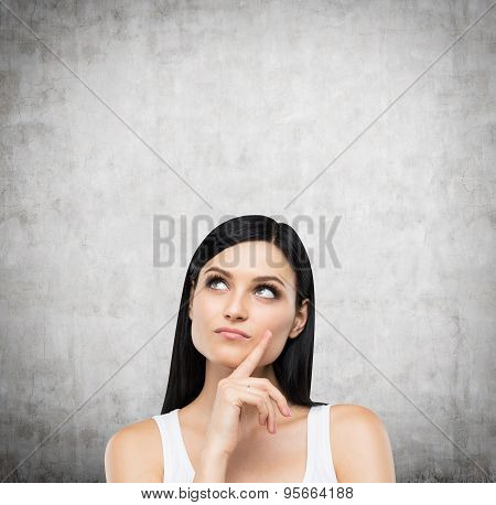 A Portrait Of A Pensive Brunette Lady In A White Tank Top. Concrete Background.
