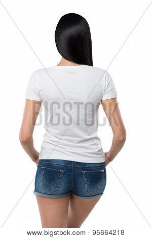 Rear View Of The Brunette Girl In Denim Shorts And White T-shirt. Isolated.